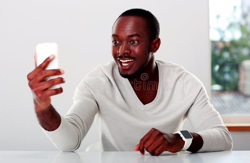 Hombre africano que mira en smartphone imagen de archivo