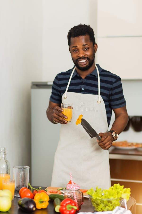 Hombre africano que prepara la comida sana en casa en cocina foto de archivo