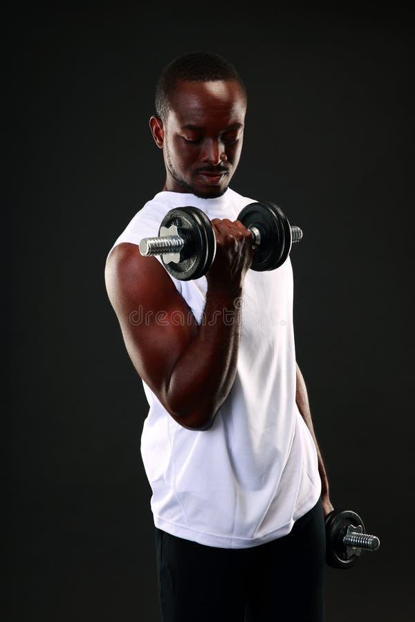 Hombre africano que se resuelve con pesas de gimnasia foto de archivo