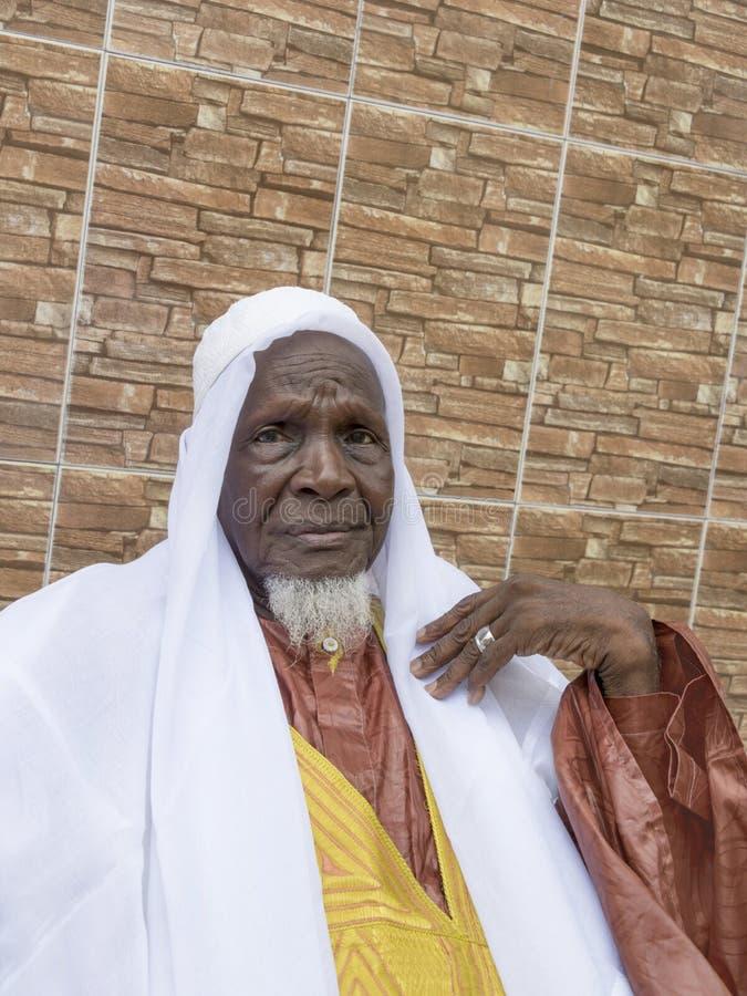 Hombre africano que se sienta delante de su casa, ochenta años foto de archivo