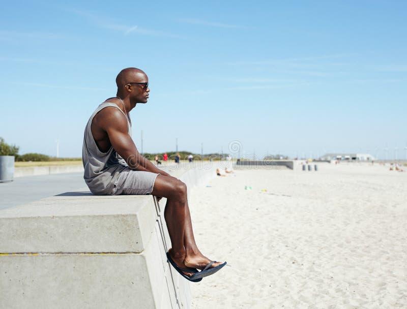 Hombre africano que se sienta en una 'promenade' de la playa foto de archivo libre de regalías