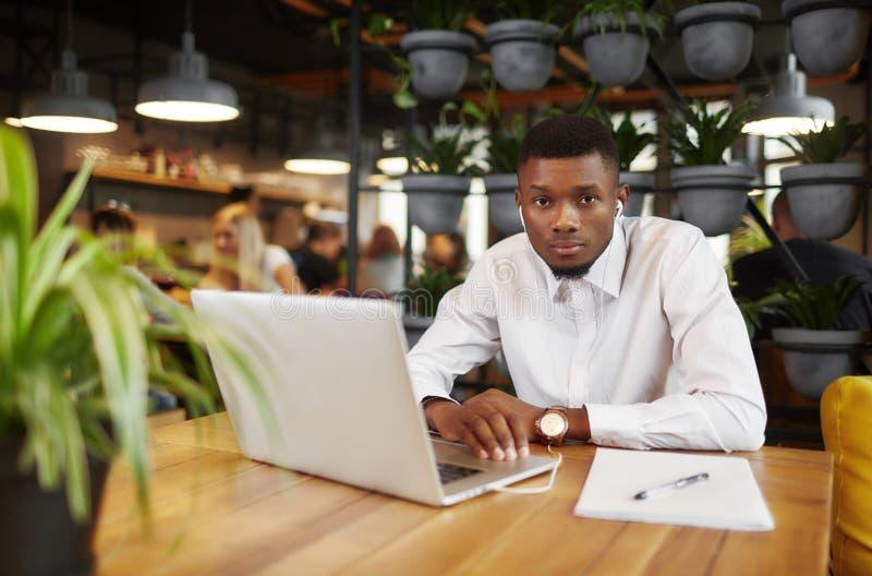 Hombre africano que trabaja en el café con el ordenador portátil fotos de archivo libres de regalías