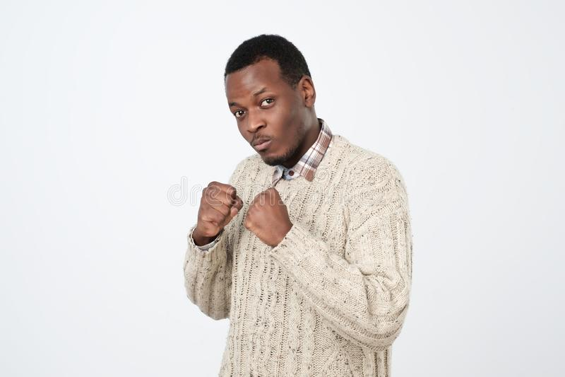 Hombre africano serio en actitud del boxeo, puños de apretón en gesto de la lucha fotografía de archivo