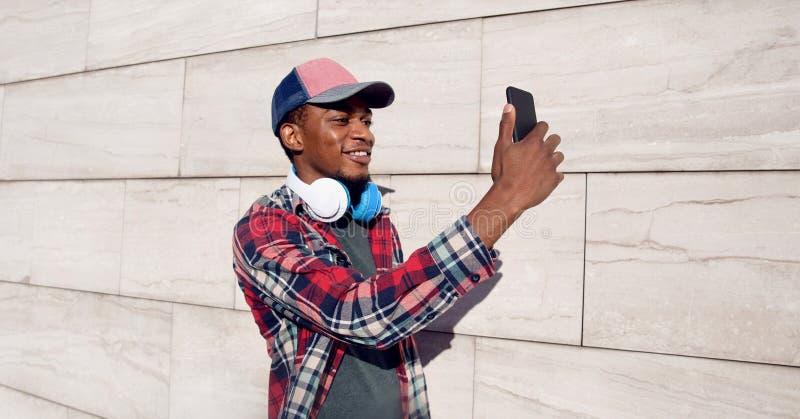 Hombre africano sonriente elegante del retrato que toma la imagen del selfie por el teléfono con los auriculares en la gorra de b fotos de archivo