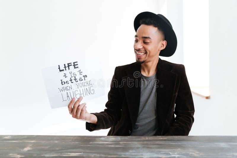 Hombre africano sonriente que sostiene la hoja de papel con palabras fotos de archivo