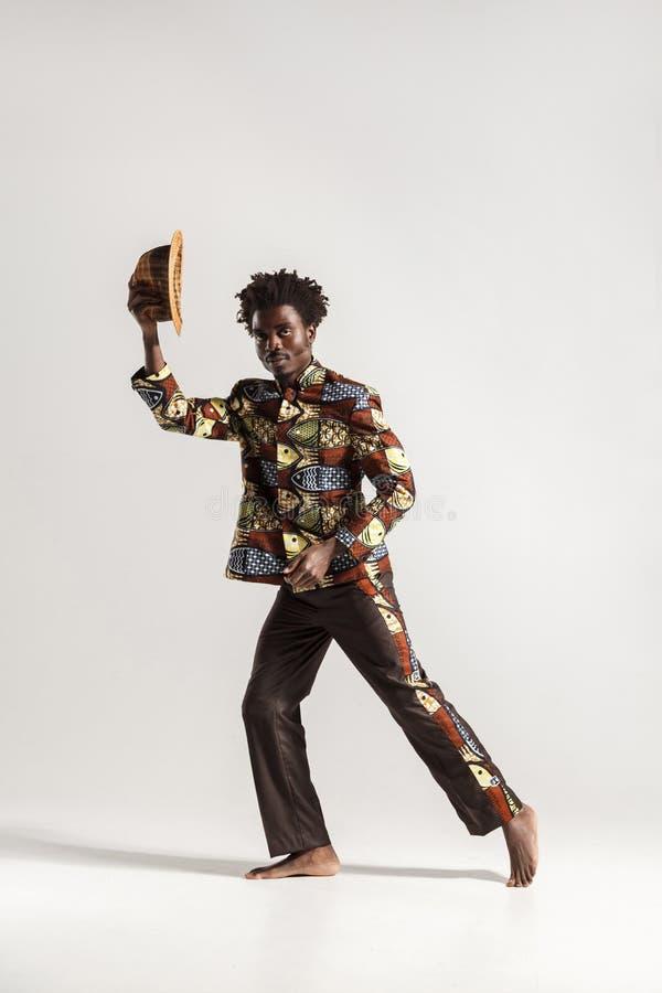 Hombre afro atractivo que sostiene el sombrero y que mira la cámara foto de archivo