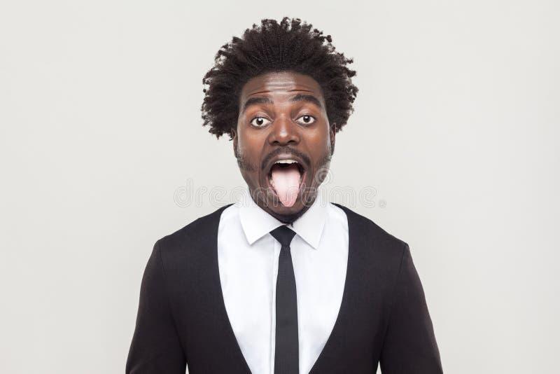 Hombre afro loco que mira la cámara y la lengua hacia fuera imagen de archivo