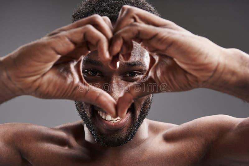 Hombre afroamericano alegre que expresa amor mientras que sonríe imágenes de archivo libres de regalías