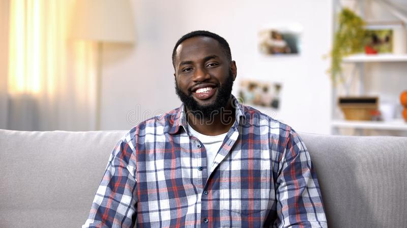 Hombre afroamericano alegre que se sienta en el sofá y que mira la cámara, relajándose fotografía de archivo