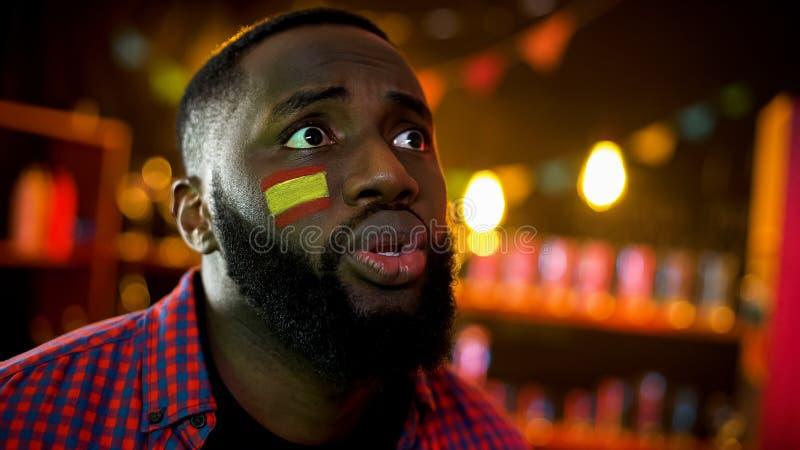 Hombre afroamericano ansioso con la bandera española en el equipo de deporte favorable de la mejilla fotografía de archivo