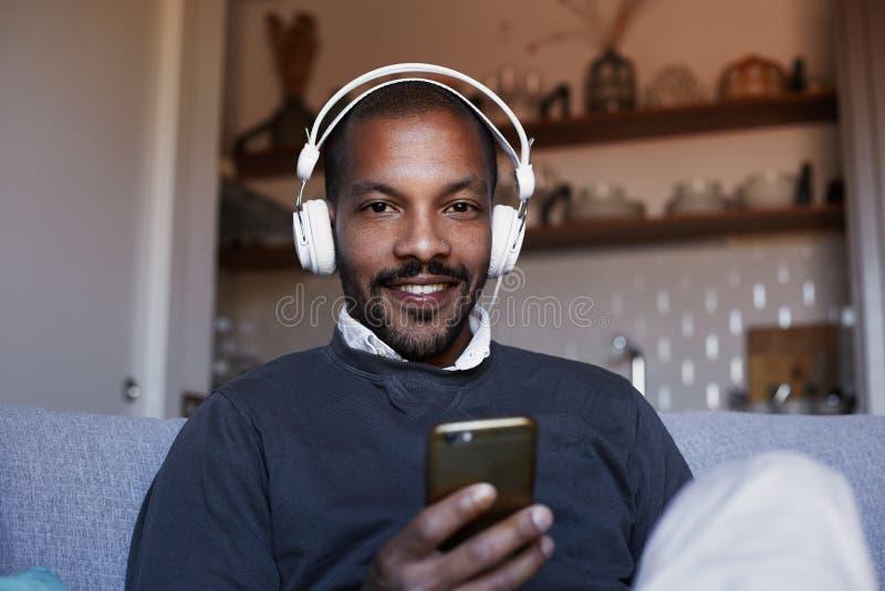 Hombre afroamericano atractivo con los auriculares blancos que escucha la música en su teléfono Concepto de relajación imagenes de archivo
