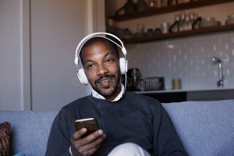 Hombre afroamericano atractivo con los auriculares blancos que escucha la música en su teléfono Concepto de relajación foto de archivo libre de regalías