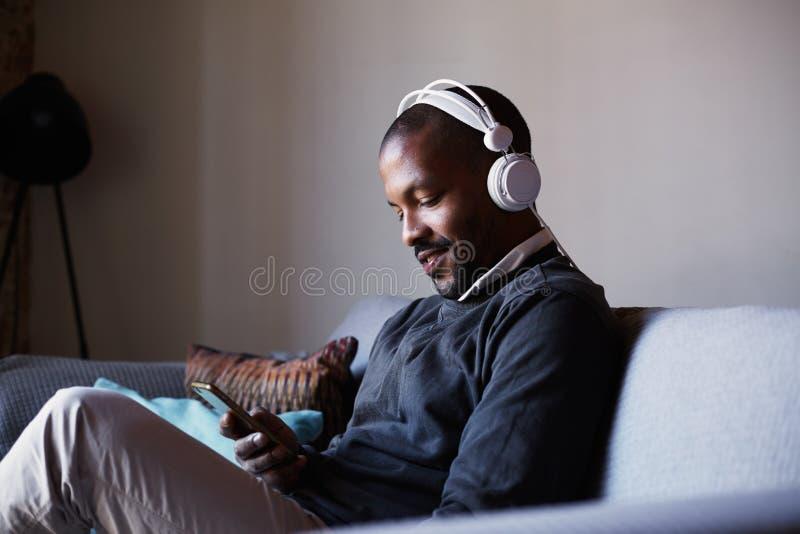 Hombre afroamericano atractivo con los auriculares blancos que escucha la música en su teléfono Concepto de relajación imagen de archivo