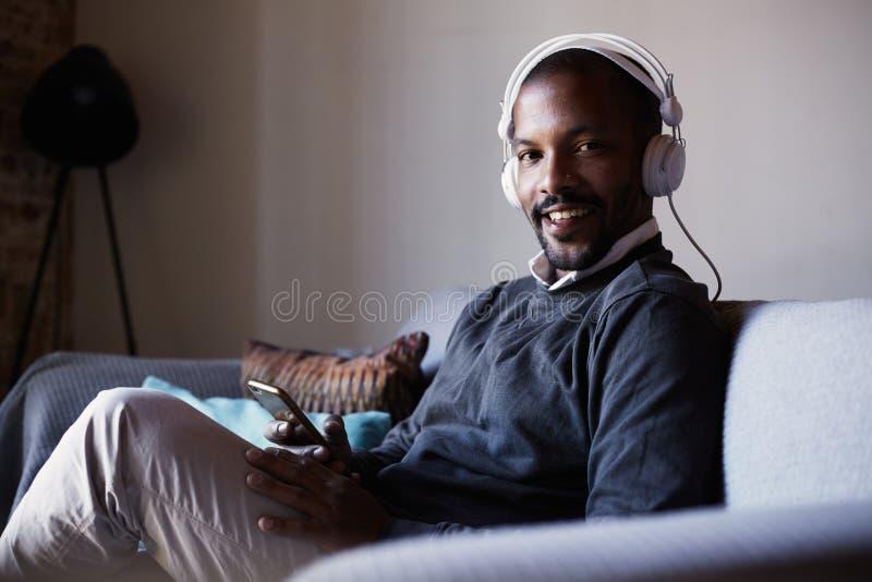 Hombre afroamericano atractivo con los auriculares blancos que escucha la música en su teléfono Concepto de relajación fotografía de archivo