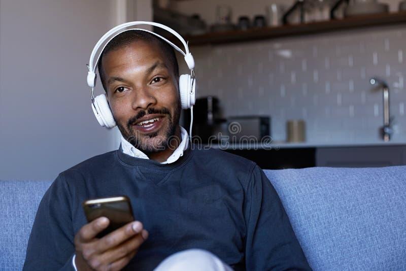 Hombre afroamericano atractivo con los auriculares que escucha la música en su teléfono Concepto de relajación imagen de archivo