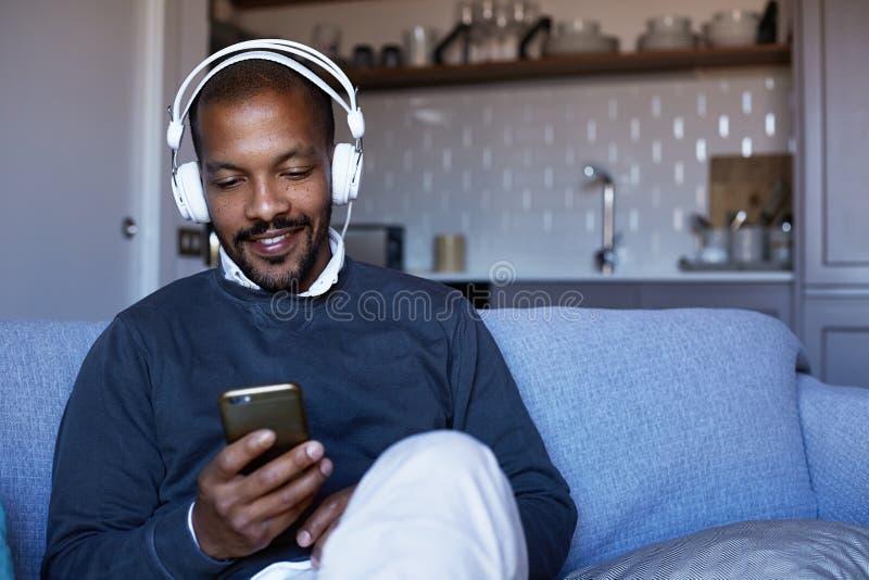 Hombre afroamericano atractivo con los auriculares que escucha la música en su teléfono Concepto de relajación foto de archivo libre de regalías