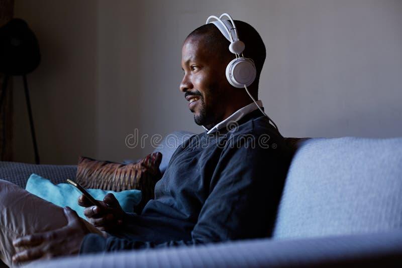 Hombre afroamericano atractivo con los auriculares que escucha la música en su teléfono Concepto de relajación imagenes de archivo