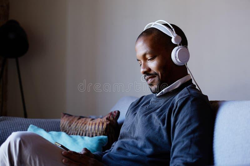 Hombre afroamericano atractivo con los auriculares que escucha la música en su teléfono Concepto de relajación imagen de archivo libre de regalías