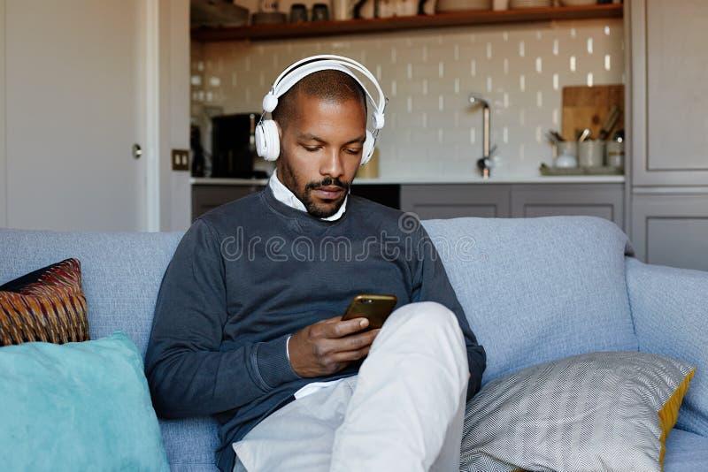 Hombre afroamericano atractivo con los auriculares que escucha la música en su teléfono Concepto de relajación fotos de archivo