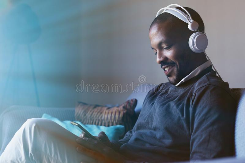 Hombre afroamericano atractivo con los auriculares que escucha la música en su teléfono Concepto de relajación flama imagen de archivo