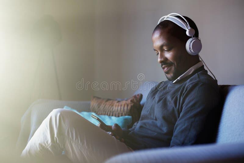 Hombre afroamericano atractivo con los auriculares que escucha la música en su teléfono Concepto de relajación flama imágenes de archivo libres de regalías
