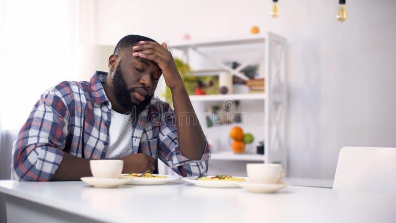 Hombre afroamericano cansado que tiene dolor de cabeza después del día duro, sensación agotada imagen de archivo