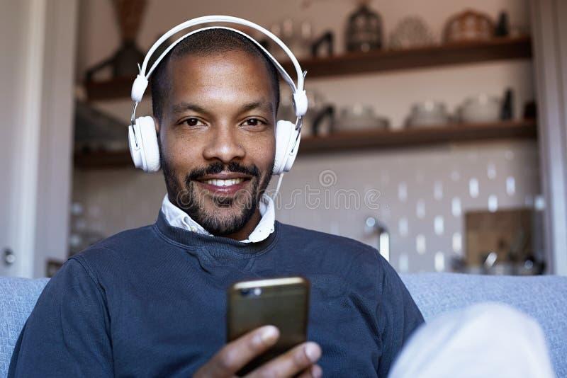 Hombre afroamericano confiado con los auriculares que escucha la música en su teléfono Concepto de relajación foto de archivo
