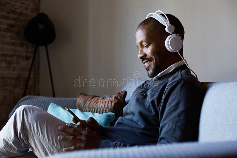 Hombre afroamericano confiado con los auriculares que escucha la música en su teléfono Concepto de relajación foto de archivo libre de regalías