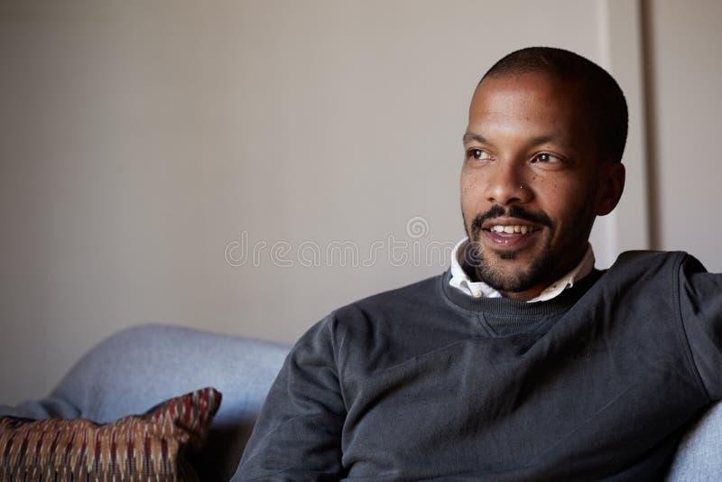 Hombre afroamericano confiado que se sienta en el sofá del sofá en la sala de estar fotografía de archivo