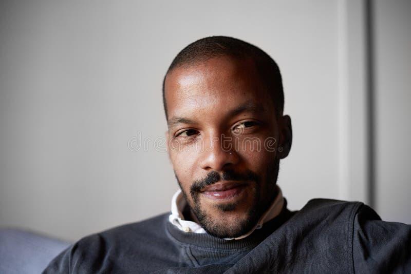 Hombre afroamericano confiado que se sienta en el sofá del sofá en la sala de estar imágenes de archivo libres de regalías