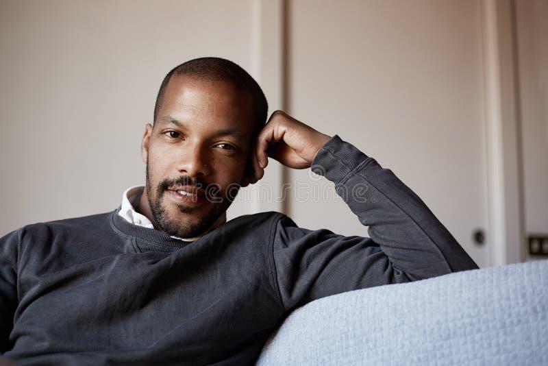 Hombre afroamericano confiado que se sienta en el sofá del sofá en la sala de estar fotos de archivo
