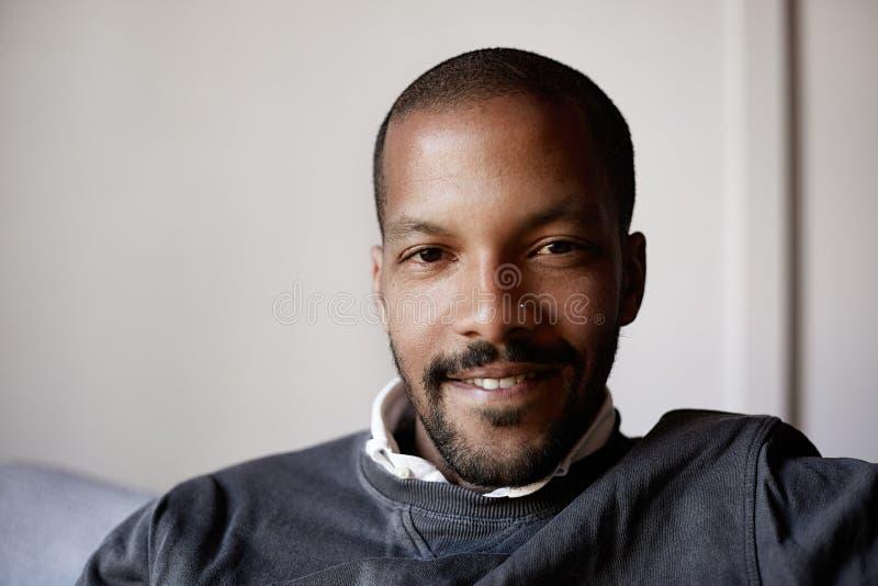 Hombre afroamericano confiado que se sienta en el sofá del sofá en la sala de estar foto de archivo