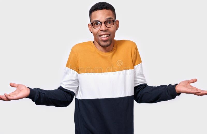 Hombre afroamericano confuso de los jóvenes que encoge con las manos aumentadas cerca de los hombros que sonríen con mirada trist foto de archivo