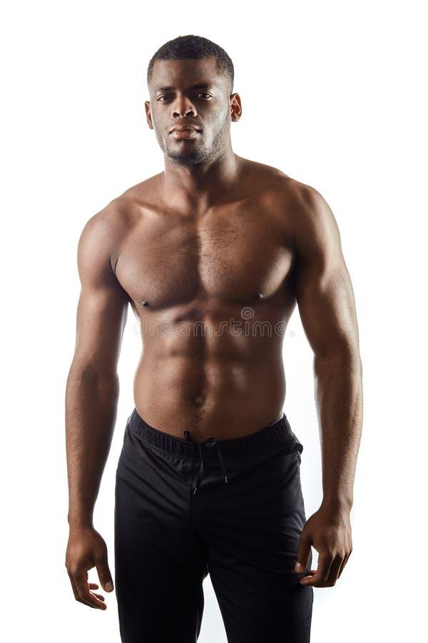 Hombre afroamericano delgado descamisado fresco en la ropa de deportes que mira la cámara imagen de archivo