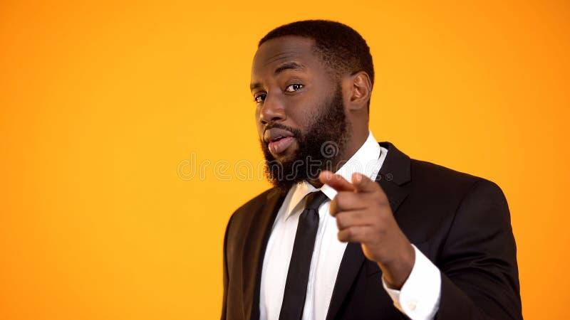 Hombre afroamericano elegante confiado en traje que se?ala con el finger, fechando el sitio foto de archivo