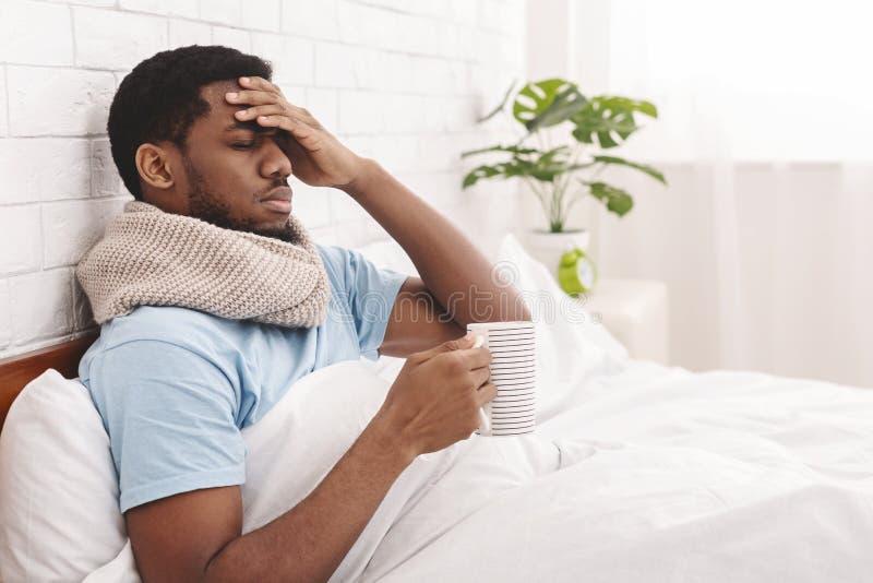 Hombre afroamericano enfermo que bebe té curativo caliente en cama imagenes de archivo