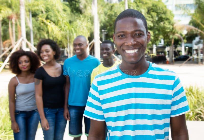 Hombre afroamericano feliz con el grupo de personas de África imagen de archivo