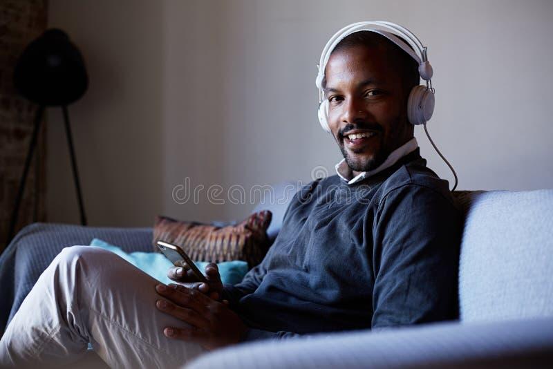 Hombre afroamericano feliz con los auriculares que escucha la música en su teléfono Concepto de relajación fotografía de archivo