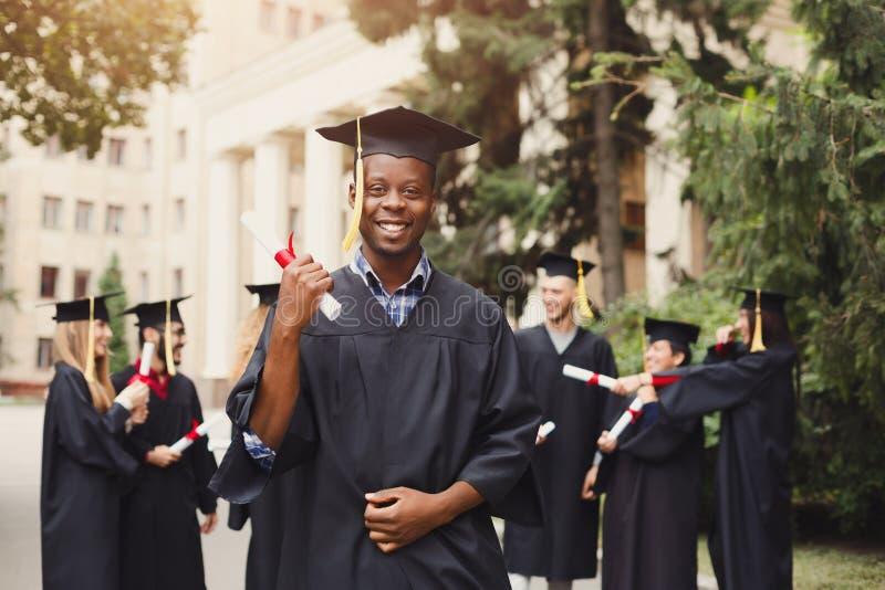 Hombre afroamericano feliz en su día de graduación foto de archivo