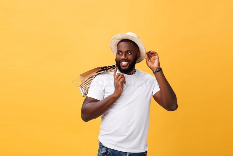 Hombre afroamericano feliz que sostiene bolsos de compras en fondo amarillo Concepto de los días de fiesta fotos de archivo