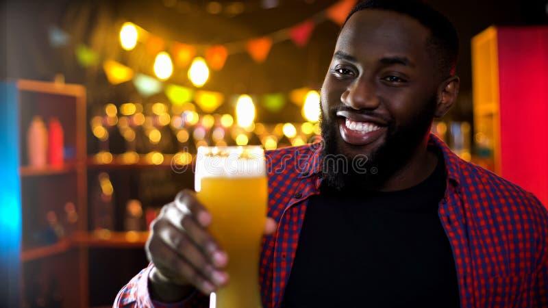 Hombre afroamericano feliz que sostiene el vidrio con la cerveza ligera fresca y fría, pasatiempo imagen de archivo libre de regalías