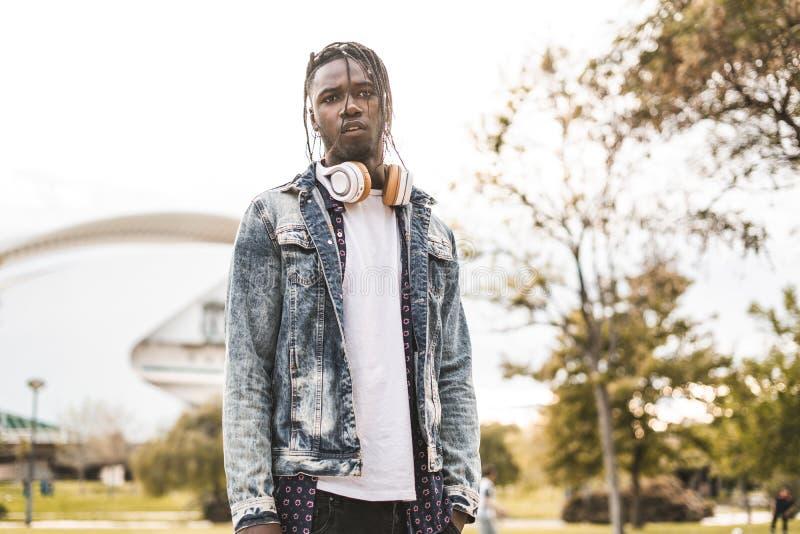Hombre afroamericano hermoso del retrato y hombre joven feliz con la calle de los auriculares de la música fotografía de archivo libre de regalías