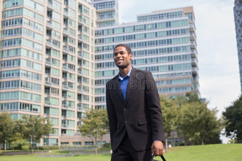 Hombre afroamericano hermoso joven que camina para trabajar, mirando estafa imágenes de archivo libres de regalías