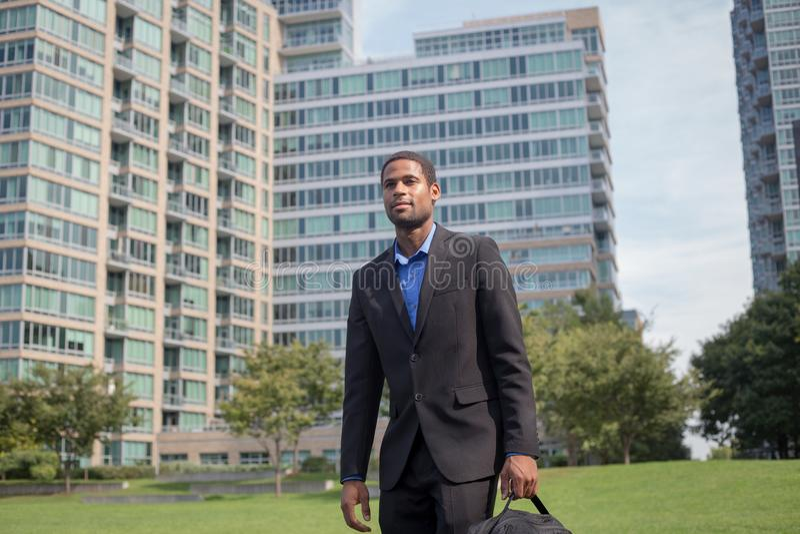 Hombre afroamericano hermoso joven que camina para trabajar, mirando sha fotos de archivo libres de regalías