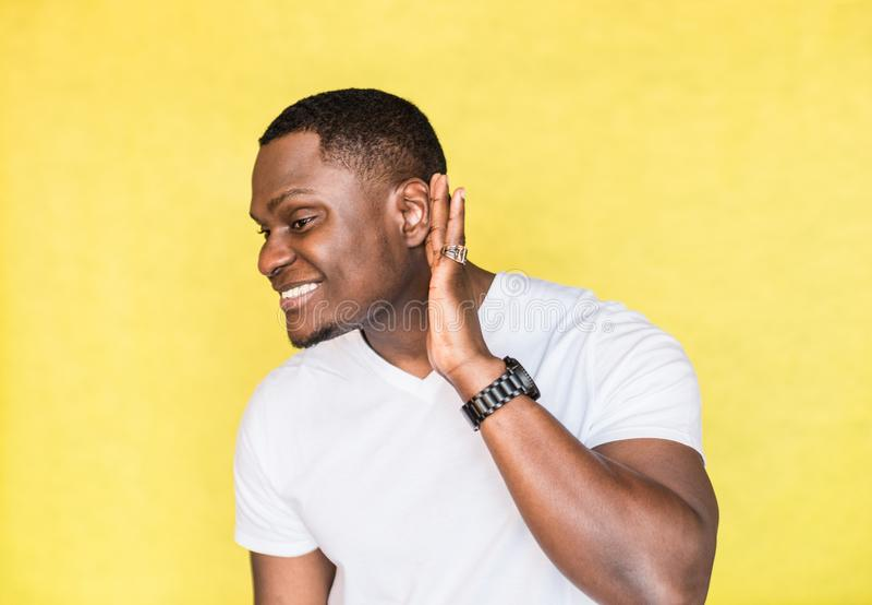 Hombre afroamericano hermoso joven que intenta o?r mejor atando su palma al o?do fotografía de archivo