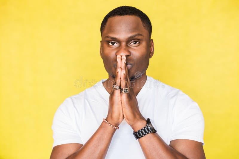 Hombre afroamericano hermoso que presiona las palmas juntas en gesto de rogaci?n Rogaci?n para la salud imagen de archivo libre de regalías