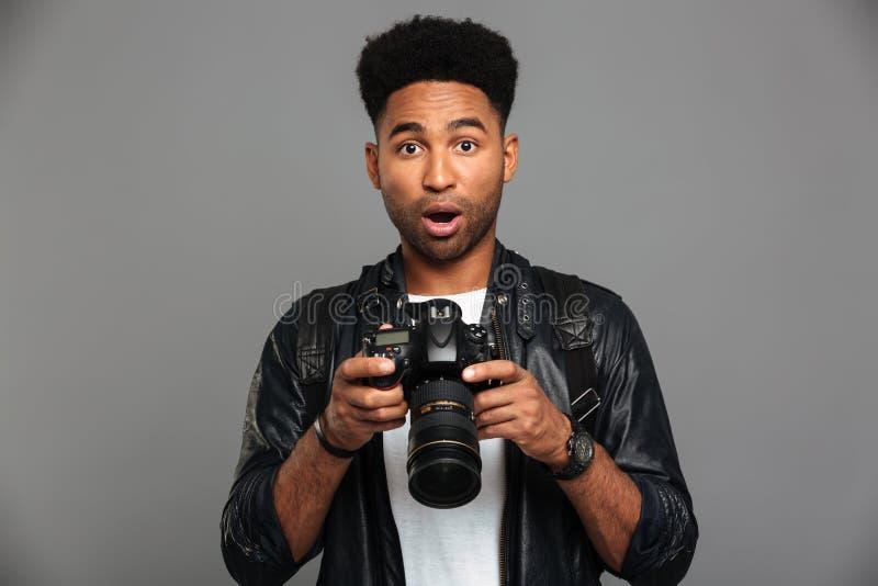 Hombre afroamericano hermoso sorprendente en la chaqueta de cuero que sostiene digi fotos de archivo