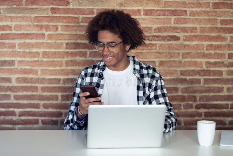 Hombre afroamericano joven hermoso con las lentes usando su smartphone mientras que trabaja con el ordenador portátil en casa imagen de archivo