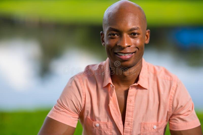 Hombre afroamericano joven hermoso del retrato que sonríe en la cámara Hombre que lleva un medio camino desabrochado camisa rosad foto de archivo
