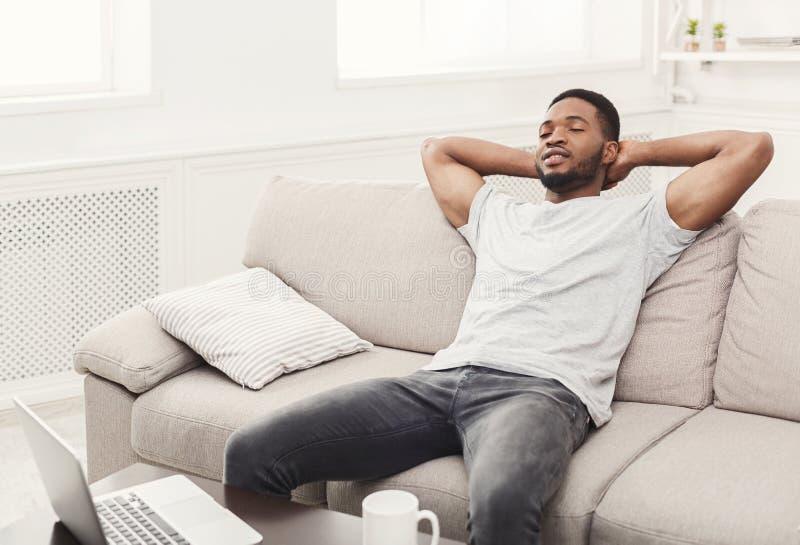 Hombre afroamericano joven hermoso que se relaja en el sofá en casa imagen de archivo